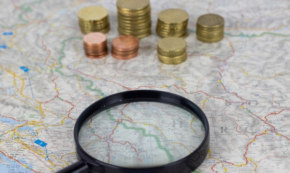 Image of map, magnifying glass and money