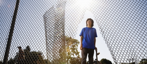 child standing in a ripped fence
